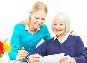 caregiver helping an elder in writing